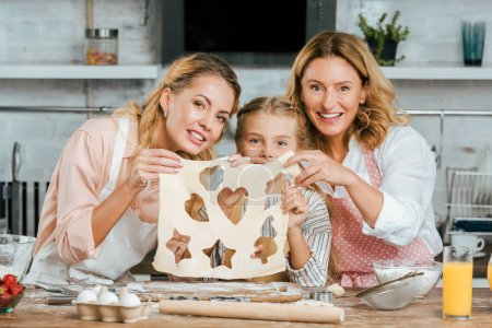 happy child with mother and grandmother holding cutted dough with heart, star and christmas tree shaped holes at home