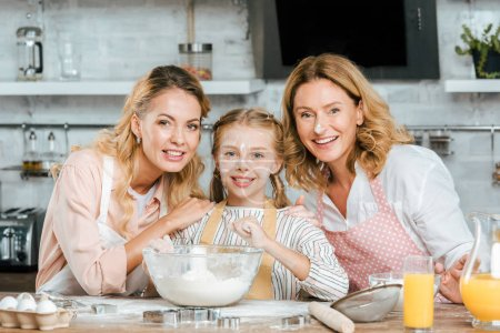happy little child preparing dough with mother and grandmother at home and looking at camera
