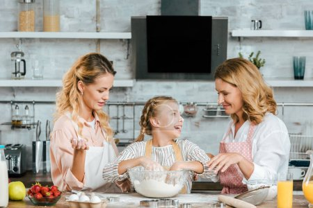 happy little child preparing dough with mother and grandmother at home
