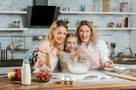 happy child clapping hands with flour while cooking with mother and grandmother at home