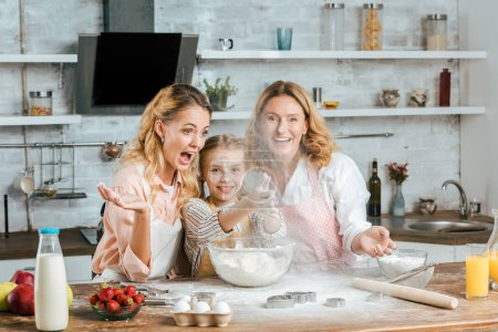 smiling child clapping hands with flour while cooking with mother and grandmother at home