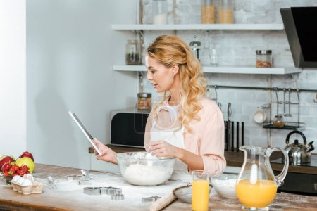 Photo for Beautiful young woman making dough and using tablet at kitchen - Royalty Free Image