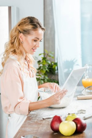 Photo for Attractive young woman making dough and using tablet at home - Royalty Free Image
