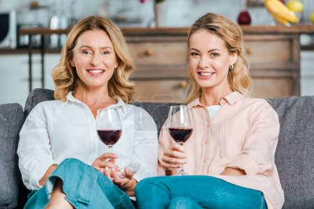 happy mature mother and adult daughter with glasses of red wine spending time together at home and looking at camera