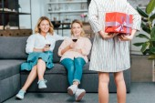 cropped shot of child hiding present behind back while mother and grandmother sitting on couch on background
