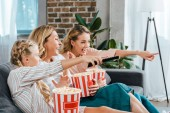excited child with mother and grandmother watching movie on couch at home with buckets of popcorn and pointing at screen