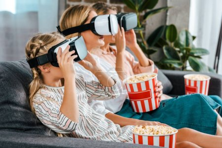 Photo for Side view of child with mother and grandmother sitting on couch together and watching movie with virtual reality headsets at home - Royalty Free Image
