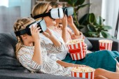 side view of child with mother and grandmother sitting on couch together and watching movie with virtual reality headsets at home