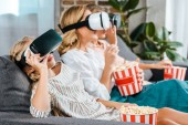 little child with mother and grandmother sitting on couch together and watching movie with virtual reality headsets at home