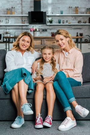 child with mother and grandmother sitting on couch together and watching tv at home