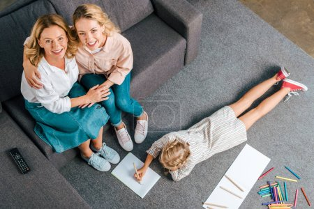 high angle view of happy mother and grandmother sitting on couch while child drawing on floor at home