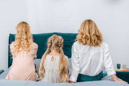 rear view of child with mother and grandmother sitting on bed at home