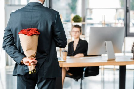 Photo for Cropped image of businessman hiding bouquet of roses behind back to surprise businesswoman in office - Royalty Free Image