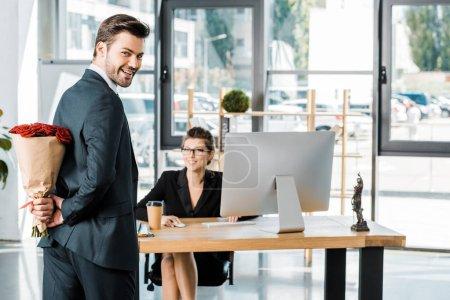 Foto de Sonriendo el ramo de escondite de empresario de rosas detrás para sorprender a empresaria en oficina - Imagen libre de derechos
