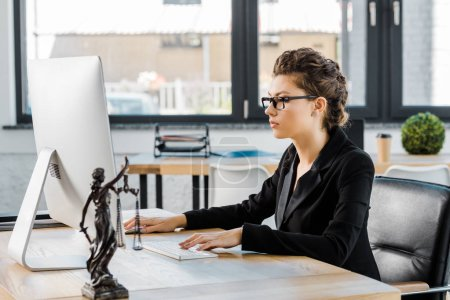attractive businesswoman in glasses working with computer at table in office, themis statue on tabletop