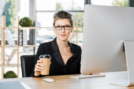 Foto de Atractiva empresaria en vasos trabajando con ordenador en la mesa en la oficina y sosteniendo la taza de café desechables - Imagen libre de derechos