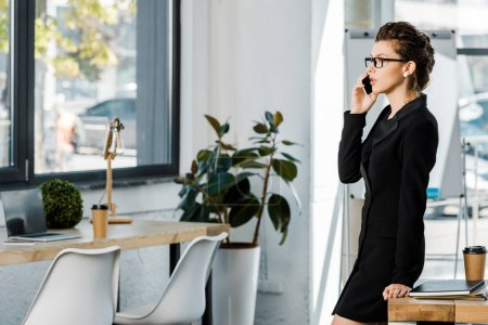 side view of beautiful businesswoman in formal wear leaning on table and talking by smartphone in office