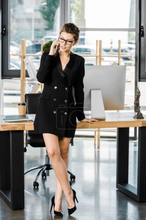 attractive businesswoman in glasses leaning on table and talking by smartphone in office