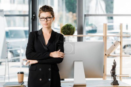 portrait of attractive businesswoman standing with crossed arms and looking at camera in office