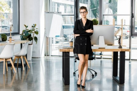 beautiful businesswoman standing with crossed arms and looking at camera in office