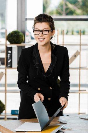sonriente atractiva empresaria sosteniendo carpeta con documentos y mirando a la cámara en la oficina