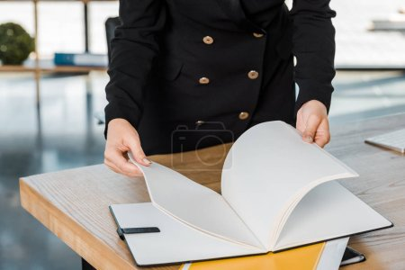 cropped image of businesswoman holding folder with documents in office
