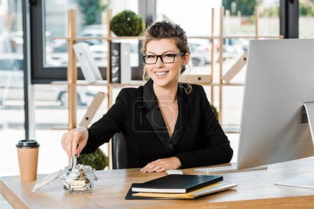 smiling attractive businesswoman putting money in glass jar with note Vacation in office, travel concept