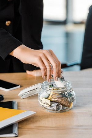 cropped image of businesswoman putting cash in glass jar with note Vacation in office, travel concept