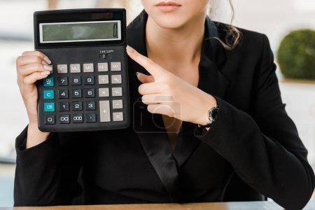 Photo pour Image recadrée de femme d'affaires pointant sur la calculatrice dans le bureau - image libre de droit