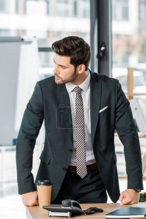Photo for Handsome businessman leaning on table in office and looking away - Royalty Free Image