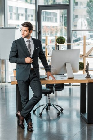 handsome businessman standing near table in office, touching jacket and looking away