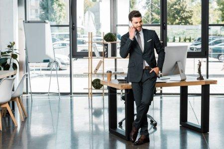 Photo pour Bel homme d'affaires gai se penchant sur la table et de parler de smartphone au bureau - image libre de droit