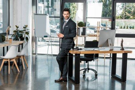 Photo pour Sourire de beau homme d'affaires se penchant sur la table et la tenue des smartphone dans Bureau - image libre de droit