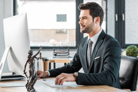 handsome lawyer working with computer at table in office, themis statue on tabletop