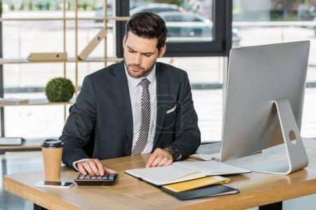 Foto de Hombre de negocios guapo serio usando calculadora en la mesa en la oficina - Imagen libre de derechos