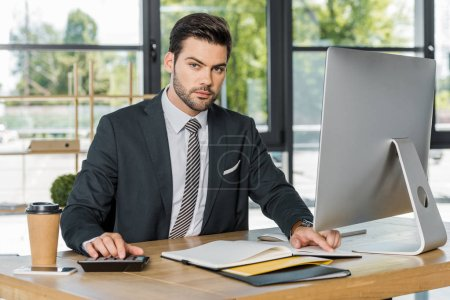 handsome businessman using calculator in office, open folder on tabletop