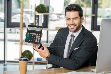 smiling handsome businessman showing calculator at table in office and looking at camera