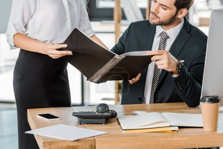 cropped image of businesswoman showing folder with documents to businessman in office