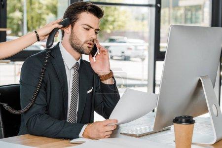 Photo pour Homme d'affaires, parler de smartphone et de la Secrétaire en lui donnant le combiné du téléphone fixe - image libre de droit