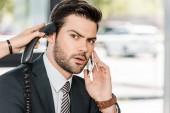 shocked businessman talking by smartphone and secretary giving him handset of stationary telephone