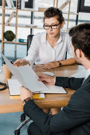 businesswoman and business partner with papers discussing work at workplace in office