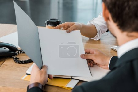 Photo for Partial view of businesswoman and business partner with papers discussing work at workplace in office - Royalty Free Image