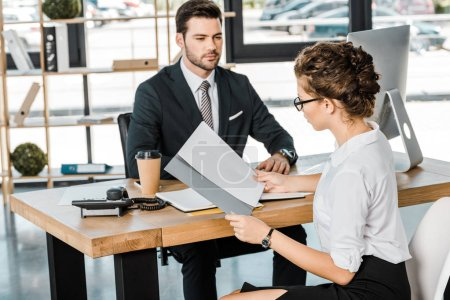 businessman and business partner with documents discussing work at workplace in office