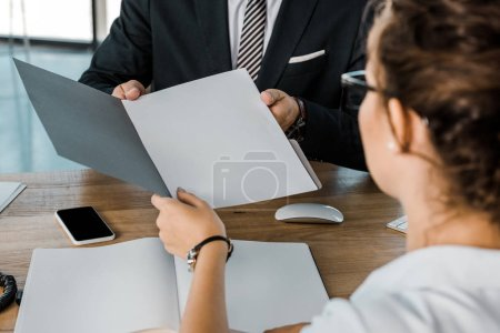 partial view of businessman and business partner with documents discussing work at workplace in office