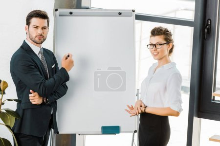 Photo for Portrait of young business colleagues standing at empty white board in office - Royalty Free Image
