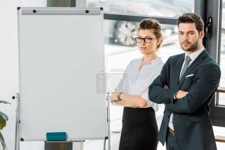 Photo for Portrait of young business colleagues with arms crossed standing at empty white board in office - Royalty Free Image