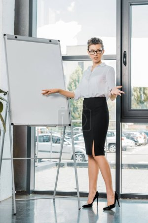 Photo for Young businesswoman in eyeglasses standing at white board in office - Royalty Free Image