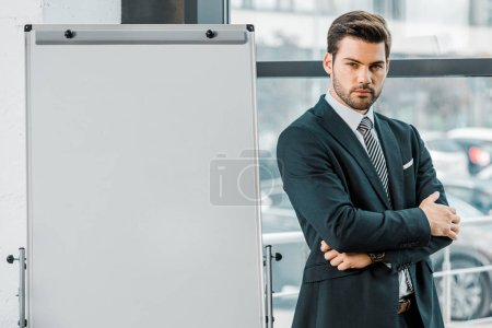 Photo for Portrait of confident businessman in suit standing at empty white board in office - Royalty Free Image