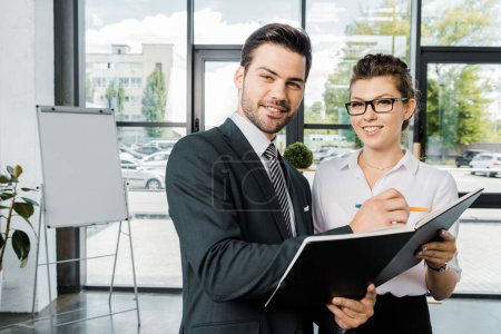 portrait of smiling businessman signing papers with colleague near by  in office