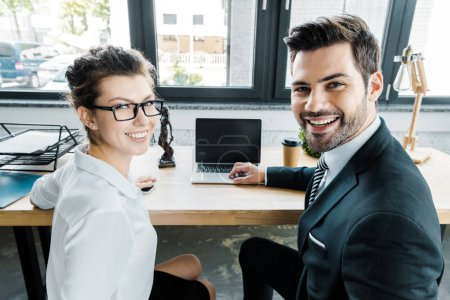 smiling lawyers at workplace with laptop with blank screen and femida in office